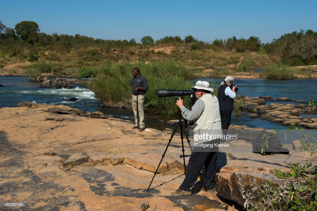 Tourists photographing on the river bank of the Sabie River in the Sabi Sands Game Reserve adjacent to the Kruger National Park in South Africa