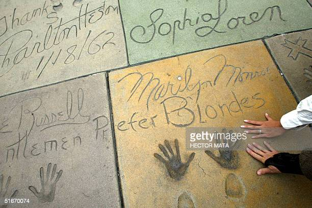 Tourists place their hands on a cement plaque depicting the hands and shoes of Marilyn Monroe at Chinese Theatre in Hollywood 24 October 2002 The...