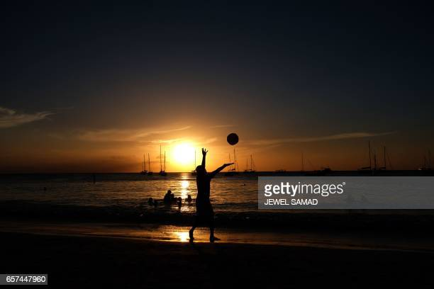 Tourists play at a beach as the sun sets in Bridgetown Barbados on March 24 2017 / AFP PHOTO / Jewel SAMAD