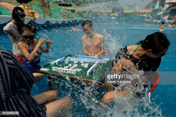 Tourists play mahjong and Chinese chess in the pool in a water park on August 08 2017 in Chongqing China The temperature stood above 40 degrees...