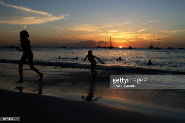 Tourists play on a beach in Bridgetown Barbados as the sun sets on March 24 2017 / AFP PHOTO / Jewel SAMAD