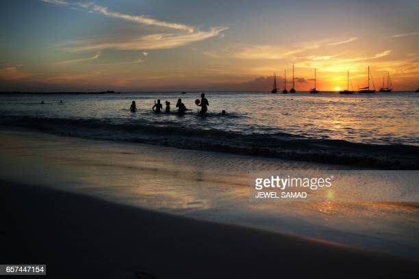 Tourists play on the water along a beach as the sun sets in Bridgetown Barbados on March 24 2017 / AFP PHOTO / Jewel SAMAD