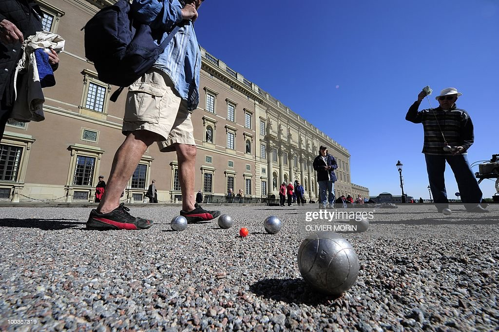 Tourists play petanque in front of the Royal castle in Stockholm on May 24, 2010. Many tourists paid a visit to the Swedish capital less than a month before Crown Princess Victoria 's wedding.
