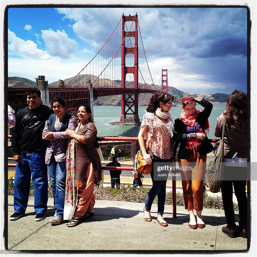 Tourists pose for a photo in front of the Golden Gate Bridge on May 25, 2012 in San Francisco, California. The Golden Gate Bridge, Highway and Transportation District is preparing for the 75th anniversary of the iconic Golden Gate Bridge that will be marked with a festival on May 26 - 27 that will feature music, displays of bridge artifacts and art exhibits. The 1.7 mile steel suspension bridge, one of the modern Wonders of the World, opened to traffic on May 27, 1937.