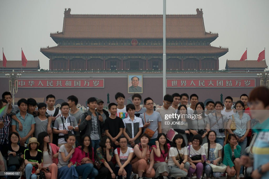 Tourists pose for a photo on Tiananmen square in Beijing on June 4, 2013. Authorities launch a major push every June 4 to prevent discussion of the violently crushed 1989 pro-democracy protests, in which at least hundreds of people died. AFP PHOTO / Ed Jones