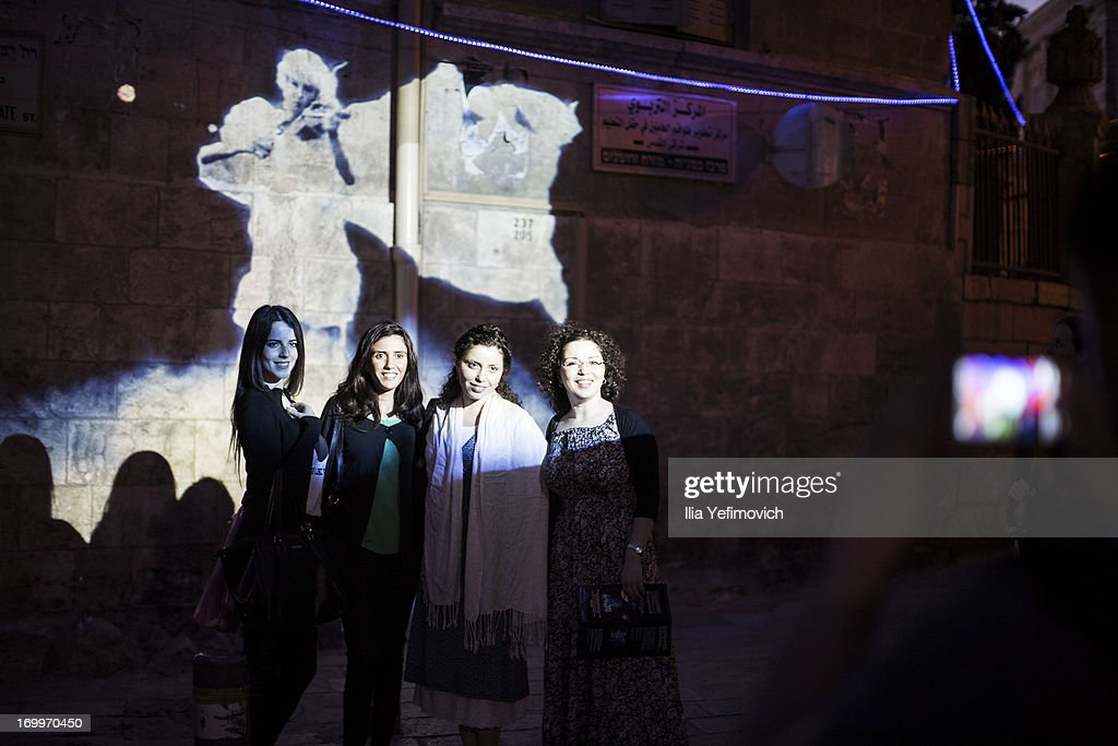 Tourists pose for a photograph during the annual Jerusalem Festival of Light on June 5, 2013 in Jerusalem, Israel. During the festival light installations are projected onto the historic buildings of Jerusalem's Old City.