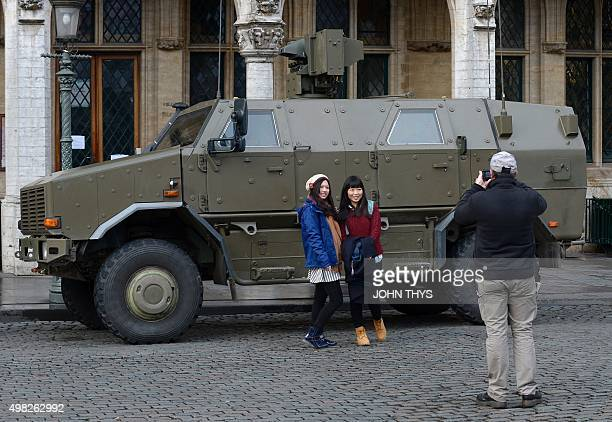 Tourists pose for a picture in front of an armoured vehicle on the Grand Place in Brussels on November 22 2015 The Belgian capital was locked down...