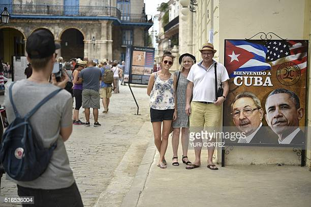 Tourists pose for a picture next to a sign placed at the entrance of a restaurant with the images of Cuban and US Presidents Raul Castro and Barack...