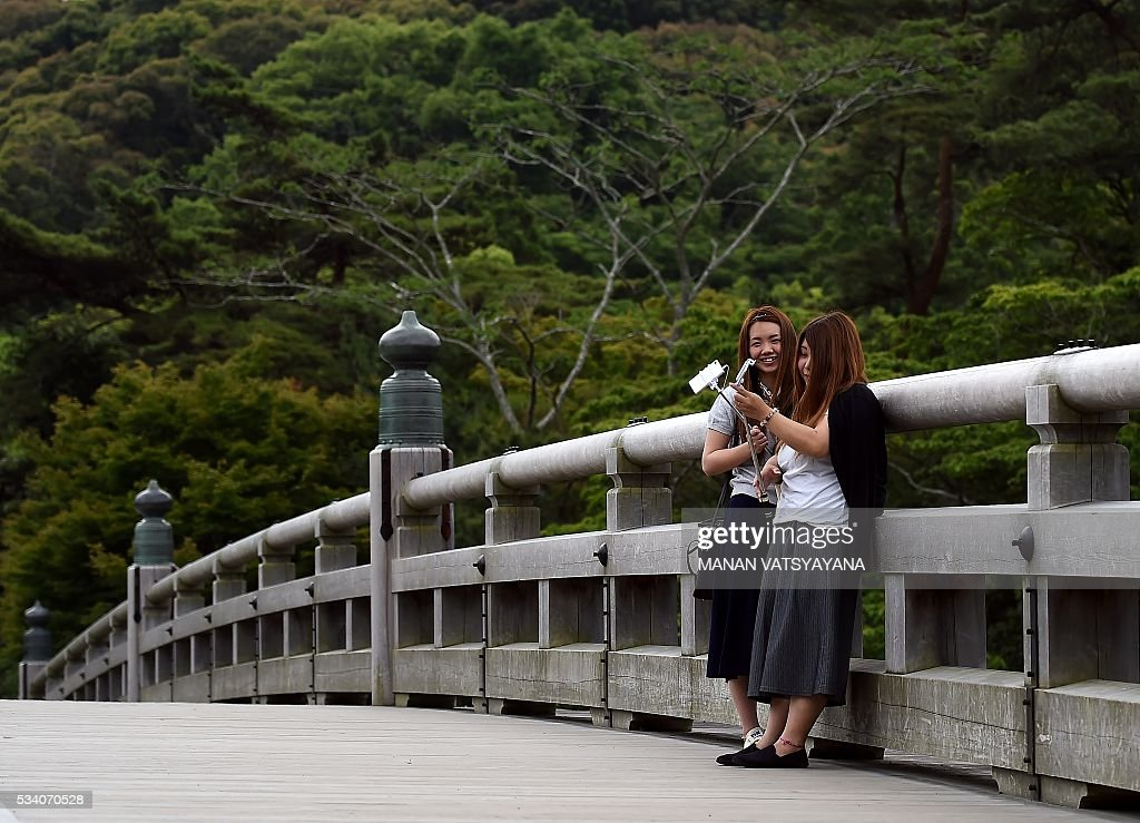Tourists pose for a selfie on the Ujibashi Bridge, leading to the Inner Shrine of the Ise Grand Shrine in Ise-Shima, 300 kilometres southwest of Tokyo on May 25, 2016, ahead of the 2016 Ise-Shima G7 Summit. The annual event, which takes place on May 26-27, draws leaders from some of the world's richest nations, including US President Barack Obama and German Chancellor Angela Merkel. VATSYAYANA