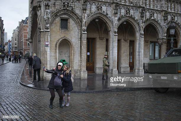 Tourists pose for a selfie photograph as a soldier patrols beside an armored vehicle in Grand Place square in Brussels Belgium on Sunday Nov 22 2015...