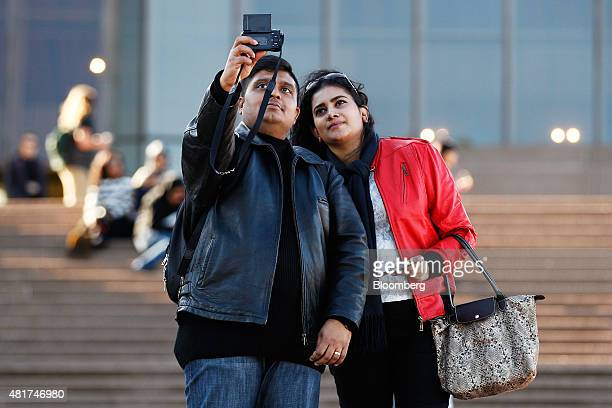 Tourists pose for a 'selfie' photograph in front of the Sydney Opera House in Sydney Australia on Tuesday July 21 2015 Tired hotels outdated...
