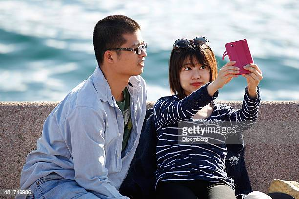 Tourists pose for a 'selfie' photograph with a smartphone in Sydney Australia on Tuesday July 21 2015 Tired hotels outdated attractions like Sydney's...