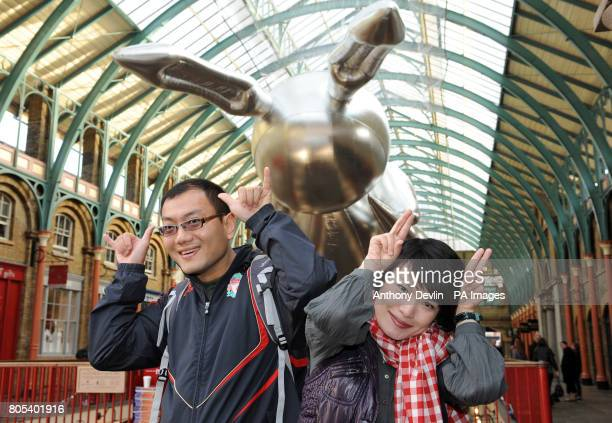 Tourists pose for photographers as Artist Jeff Koons' giant 53 foot rabbit balloon is exhibited in Covent Garden Market to publicise Pop Life Art in...