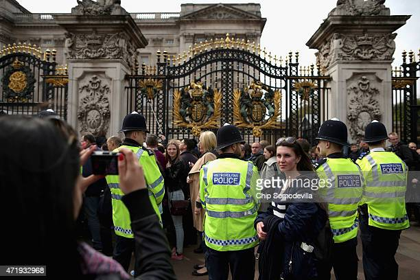 Tourists pose for photographs as Metropolitan Police officers keep an eye on the thousands of people lined up for a chance to glimpse and photograph...