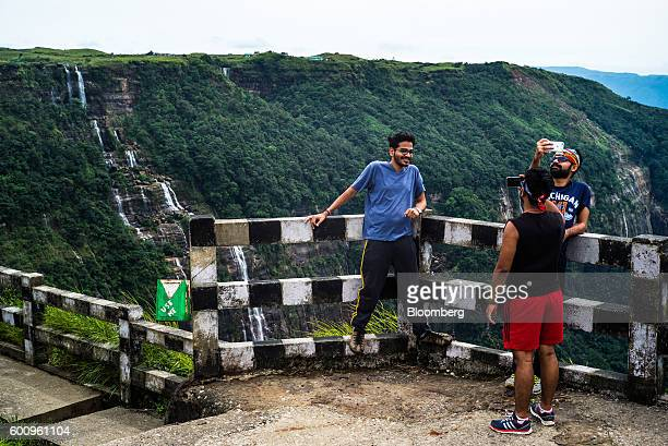 Tourists pose for photographs at Nohsngithiang Falls segmented waterfall in Cherrapunji Meghalaya India on Tuesday Aug 16 2016 Two years of deficient...