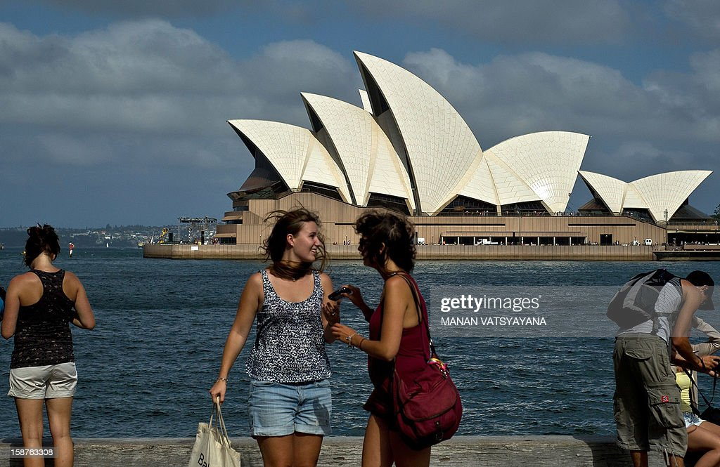 Tourists pose for photographs before the Sydney Opera House at Sydney harbour on December 28, 2012. International visitors to Australia are expected to increase from over 5.9 million in 2010/11 to nearly 8.2 million in 2020/21, an average annual growth rate of 3 percent as reported from Tourism Research Australia (TRA). AFP PHOTO / MANAN VATSYAYANA
