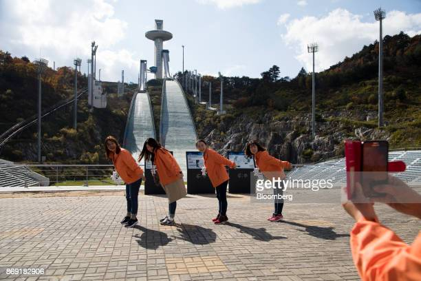 Tourists pose for photographs in front of hills at the Alpensia Ski Jumping Stadium the venue for ski jumping events at the 2018 PyeongChang Winter...