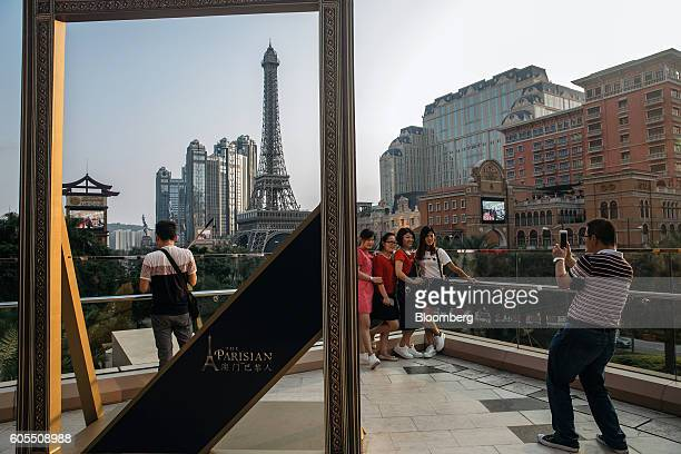Tourists pose for photographs in front of the Eiffel Tower attraction a halfsize replica of the Eiffel Tower in Paris at the Parisian Macao casino...