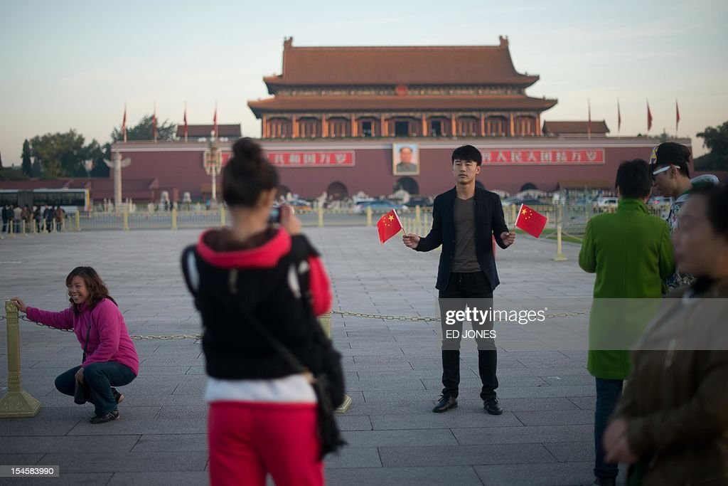 Tourists pose for photos before a portrait of Mao Zedong on Tiananmen Square early on October 23, 2012. Supporters of disgraced politician Bo Xilai have published a letter on a leftist website urging him not to be expelled from China's parliament which would pave the way for him to face trial over alleged corruption and charges. AFP PHOTO / Ed Jones