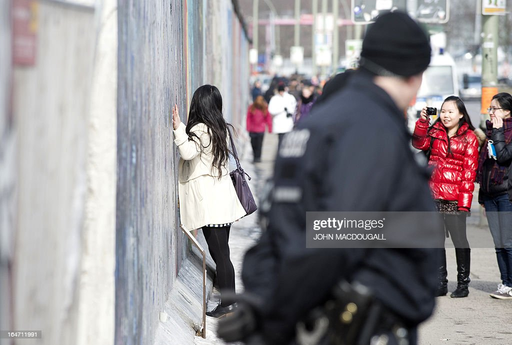 Tourists pose for pictures as two police officers guard a recently torn down stretch of the Berlin wall at the so called East Side Gallery in Berlin on March 27, 2013. A property developer removed more of the Berlin Wall early March 27, in a surprise dawn move amid a bitter running protest over the dismantling of the once-detested Cold War division, to make way for a 63-metre high residential development along the banks of the Spree river. AFP PHOTO / JOHN MACDOUGALL