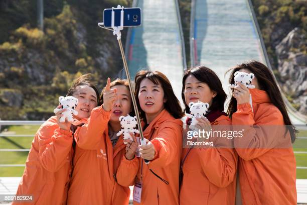 Tourists pose for selfie photographs in front of hills at the Alpensia Ski Jumping Stadium the venue for ski jumping events at the 2018 PyeongChang...