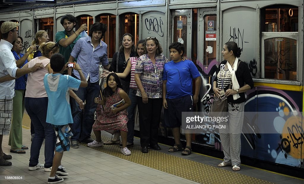 Tourists pose in front of one of the historic wagons of La Brugeoise of the subway Line A which is expected to be close soon following a decision by city mayor Mauricio Macri to replace the fleet with Chinese-made wagons, in Buenos Aires, on December 29, 2012. Line A was the first subway line to work in the southern hemisphere and its trains are among the ten oldest still working daily. The La Brugeoise wagons were constructed between 1912 and 1919 by La Brugeoise et Nicaise et Delcuve in Belgium.