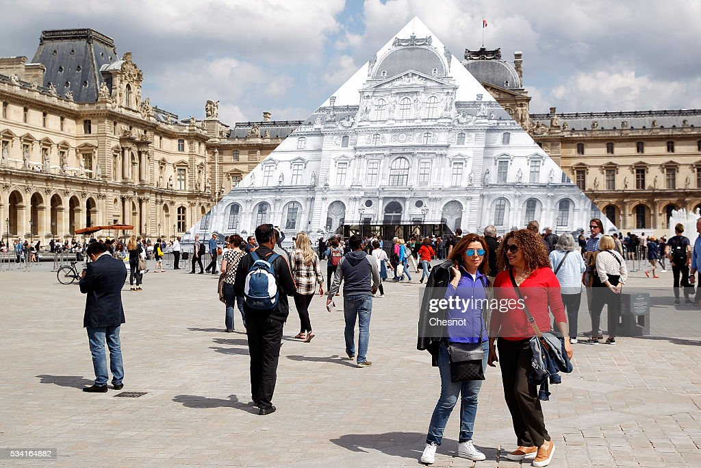 Tourists pose in front of the artwork of French street artist and photographer JR displayed on the Louvre Pyramid on May 25, 2016 in Paris France. French street artist JR has installed a huge photographic collage on the Louvre pyramid for making it disappear and creating a giant optical illusion through an anamorphosis, a technique that allows to appear or disappear a work.