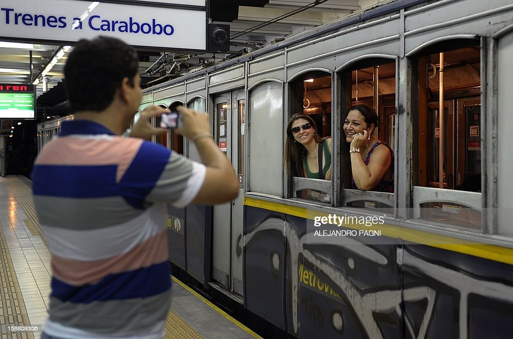 Tourists pose in one of the historic wagons of La Brugeoise of the subway Line A which is expected to be close soon following a decision by city mayor Mauricio Macri to replace the fleet with Chinese-made wagons, in Buenos Aires, on December 29, 2012. Line A was the first subway line to work in the southern hemisphere and its trains are among the ten oldest still working daily. The La Brugeoise wagons were constructed between 1912 and 1919 by La Brugeoise et Nicaise et Delcuve in Belgium.