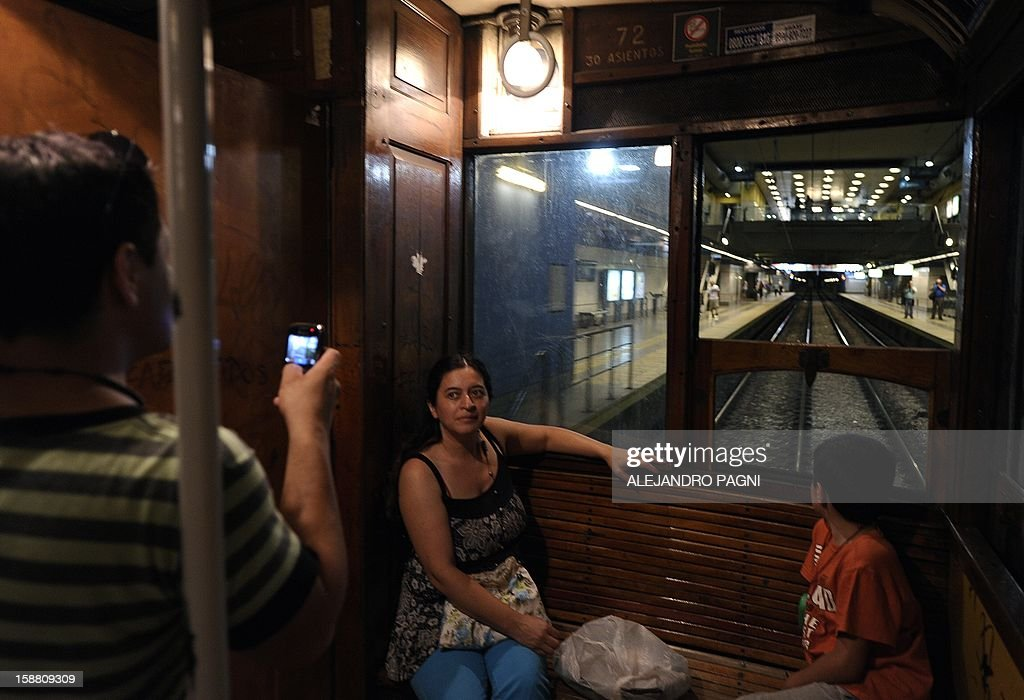Tourists pose inside one of the historic wagons of La Brugeoise of the subway Line A which is expected to be close soon following a decision by city mayor Mauricio Macri to replace the fleet with Chinese-made wagons, in Buenos Aires, on December 29, 2012. Line A was the first subway line to work in the southern hemisphere and its trains are among the ten oldest still working daily. The La Brugeoise wagons were constructed between 1912 and 1919 by La Brugeoise et Nicaise et Delcuve in Belgium. AFP PHOTO / ALEJANDRO PAGNI --- MORE PICTURES IN IMAGE FORUM