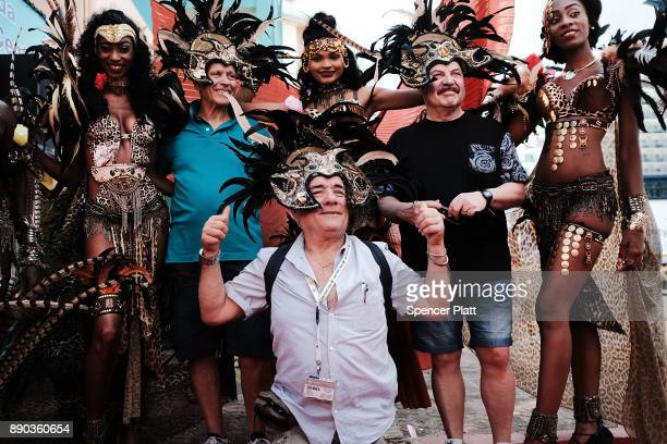 Tourists pose with local actors after arriving on a cruise ship in St John's on December 11 2017 in St John's Antigua While its sister island of...