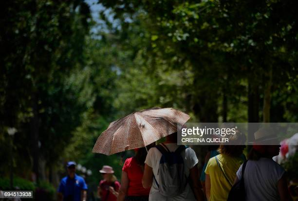 Tourists protect themselves from the sun with umbrellas and hats in Sevilla on June 10 2017 QUICLER