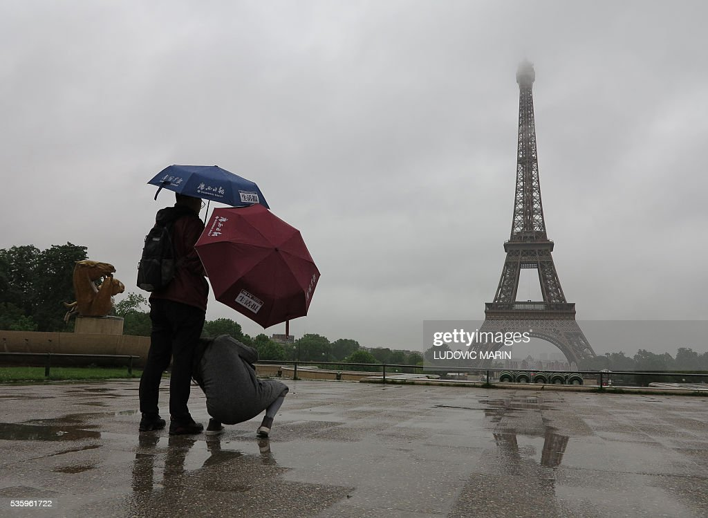 Tourists protecting themselves from the pouring rain under umbrellas take souvenir pictures of the Eiffel Tower in Paris early on May 31, 2016. / AFP / LUDOVIC