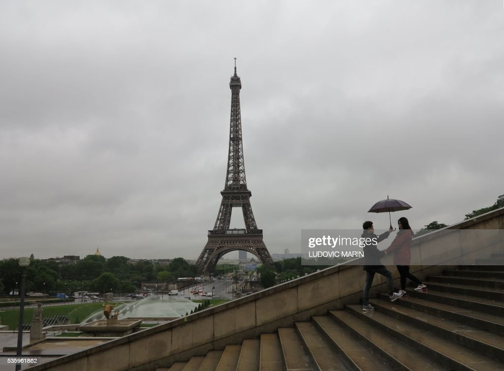 Tourists protecting themselves from the pouring rain under umbrellas walk down the Trocadero Esplanade by the Eiffel Tower in Paris early on May 31, 2016. / AFP / LUDOVIC