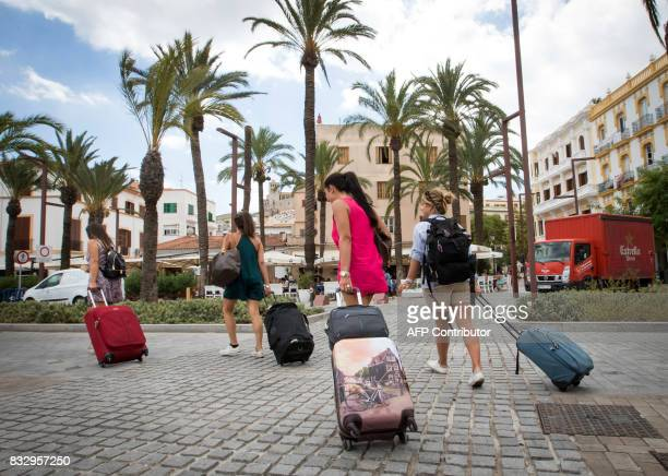 Tourists pull their suitcases in the port of Ibiza on August 11 2017 Known as much as a wild party island as a place of tranquility with coves of...