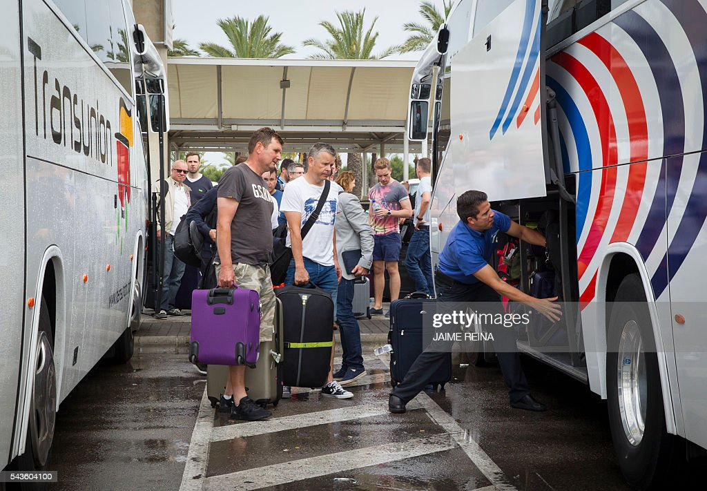 Tourists put their luggage on the bus at the Palma de Mallorca airport on June 29, 2016. As of July 1, 2016 the Balearic Island government brings launches an Ecotax, 'Ecotasa', targeting tourism businesses that will onpass the daily 0.25 Euro to two euro levy onto their clients. REINA