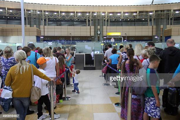Tourists queue at a security check in the airport in Egypt's Red Sea resort of Sharm ElSheikh on November 5 2015 Britain and Ireland suspended air...