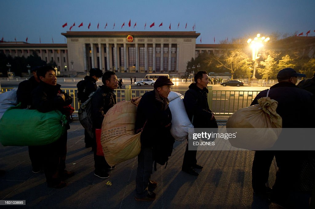 Tourists queue before the Great Hall of the People as they enter Tiananmen Square to watch the daily flag-raising ceremony in Beijing on March 5, 2013. Thousands of delegates from across China meet this week to seal a power transfer to new leaders whose first months running the Communist Party have pumped up expectations with a deluge of propaganda. AFP PHOTO / Ed Jones