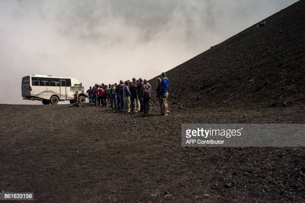 Tourists queue for a 4x4 bus shuttle on September 21 2017 on the Mount Etna volcano on the Italian island of Sicily / AFP PHOTO / Guillaume BAPTISTE