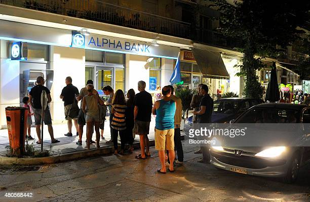 Tourists queue to withdraw cash from an automated teller machine outside an Alpha Bank AE bank branch at a tourist resort in Asprovalta Greece on...