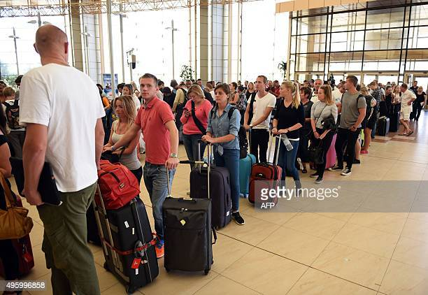 Tourists queue up at checkin counters at the airport of Egypt's Red Sea resort of Sharm ElSheikh on November 6 2015 Britain moved to repatriate...
