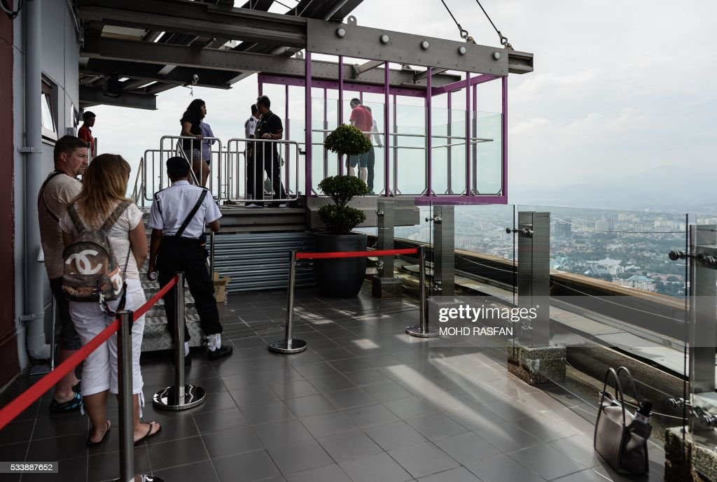 Tourists queue up for a panoramic view of the city from the Sky Box at KL Tower, the world's seventh tallest telecommunications tower, in Kuala Lumpur on May 24, 2016. Officially opened on May 20, the Sky Box has been the latest attraction for tourists arriving to the Malaysian capital. It stands 300 metres above ground and can fit six people at any one time, and offers spectacular views of the Kuala Lumpur skyline, including the iconic Petronas Twin Towers. / AFP / MOHD