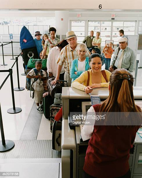 Tourists Queuing at an Airport Check-in