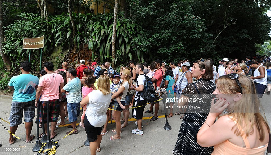 A tourists (R) reacts as she observes thousands of tourists lining up to take a van to access to the Christ the Redeemer statue, atop the Corcovado hill on January 25, 2013 in Rio de Janeiro, Brazil. During summer season around three thousand of tourists line up about three hours to visit the traditional statue.