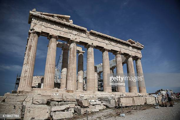 Tourists read an information board beside the ancient ruins of the Parthenon temple on Acropolis hill in Athens Greece on Thursday June 4 2015 Greek...
