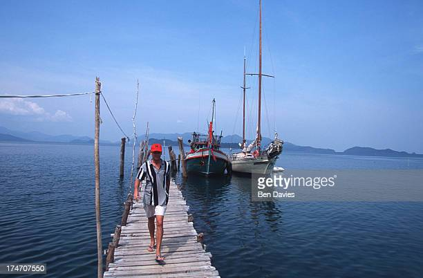Tourists relax on a luxury yacht moored alongside one of the islands of the Koh Chang National Marine Park in the Gulf of Thailand The park is made...