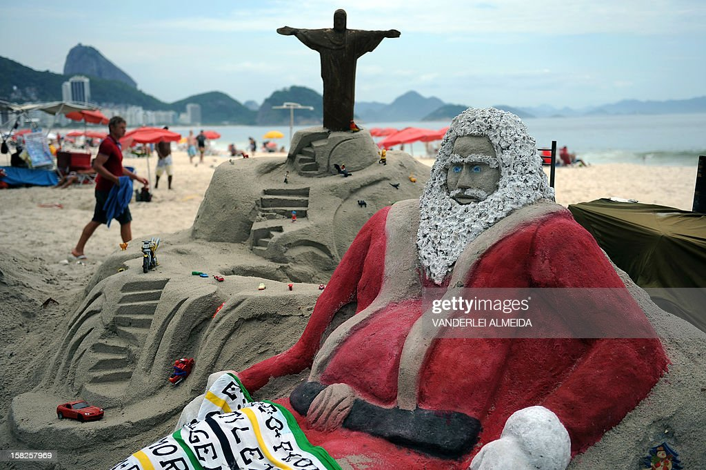 Tourists remain at Copacabana beach near a sand sculpture depicting Santa Claus in Rio de Janeiro, Brazil on December 12, 2012. High temperatures -35 to 38 degrees celcius- during the end of the spring, have taken citizens and tourists to the beaches of Rio de Janeiro. AFP PHOTO /VANDERLEI ALMEIDA