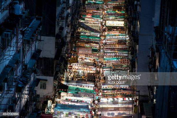 Tourists residents and vendors participate in the Temple Street night market as the popular destination is illuminated in the evening in Hong Kong on...