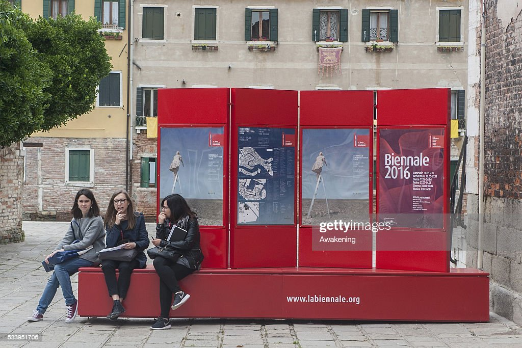 Tourists rest on a street sign of the 15th Architecture Venice BiennaleNear the Arsenale area on May 24, 2016 in Venice, Italy. The 56th International Architecture Exhibition of La Biennale di Venezia will be open to the public from May 28, 2016 in Venice, Italy.