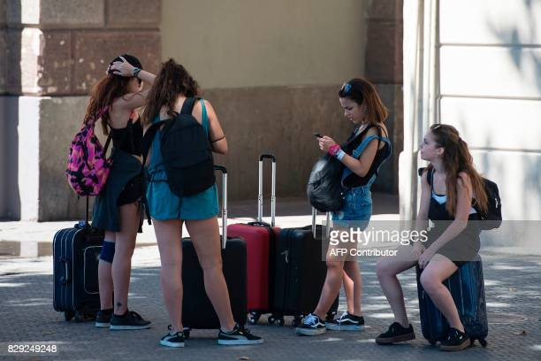 Tourists rest on their suitcases in downtown Barcelona on August 10 2017 Spanish activists in recent weeks have launched initiatives against what...