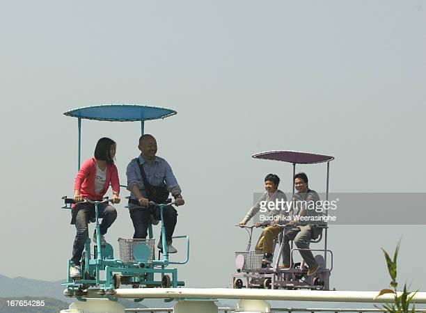 Tourists ride a pedalpowered sky cycle roller coaster at Washuzan Highland Amusement Park on April 27 2013 in Kurashiki Japan Washuzan Highland...